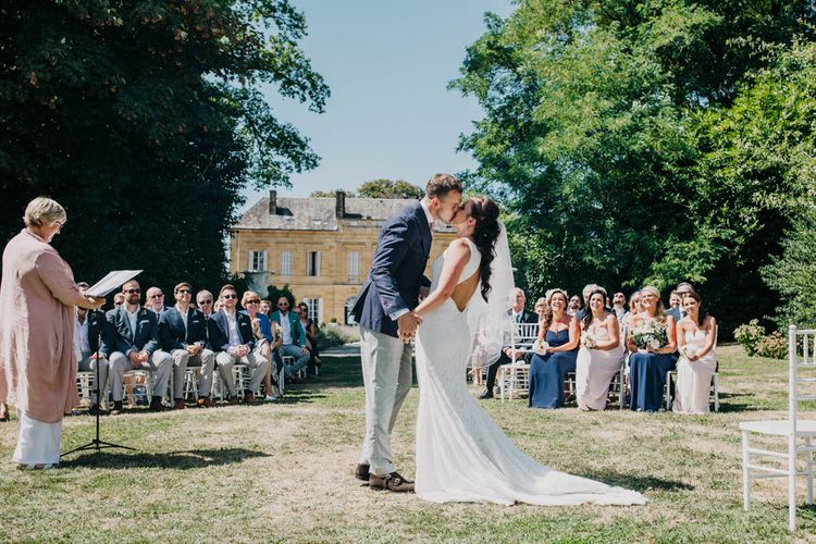 Bride in Lace Boat Neck Pronovias Wedding Dress with Keyhole Back and Fishtail Train   Fingertip Length Veil   Groom in Navy Jacket, Grey Trousers and White Shirt with Pink Tie from Suit Supply   Bridesmaids in Strapless Navy or Pink Dresses from ASOS   Outdoor Wedding Ceremony at Chateau La Durantie, Dordogne   Outdoor Seating Area and Macaroon Tower at French Chateau Wedding   Lush Imaging