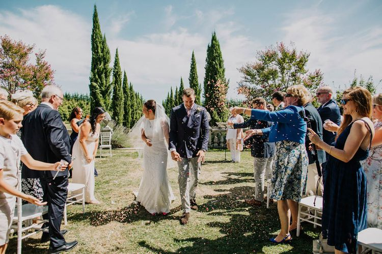 Bride in Lace Boat Neck Pronovias Wedding Dress with Keyhole Back and Fishtail Train   Fingertip Length Veil   Groom in Navy Jacket, Grey Trousers and White Shirt with Pink Tie from Suit Supply   Outdoor Wedding Ceremony at Chateau La Durantie, Dordogne   Outdoor Seating Area and Macaroon Tower at French Chateau Wedding   Lush Imaging