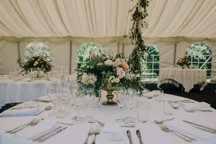 Table Centrepiece of Blush and White Flowers with Foliage in Gold Urn   Foliage Garland Wrapped Around Marquee Pole   Gold Cutlery   Outdoor Seating Area and Macaroon Tower at French Chateau Wedding   Lush Imaging