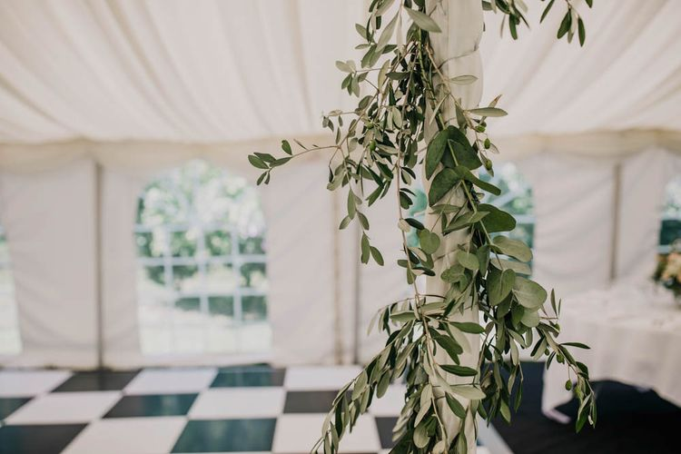 Foliage Garland Wrapped Around Marquee Pole   Outdoor Seating Area and Macaroon Tower at French Chateau Wedding   Lush Imaging