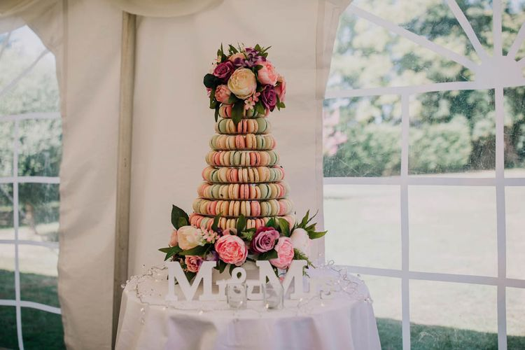 Pastel Macaroons in Tower Decorated with Pink Flowers   Mr & Mrs Sign   Fairy Lights   Outdoor Seating Area and Macaroon Tower at French Chateau Wedding   Lush Imaging