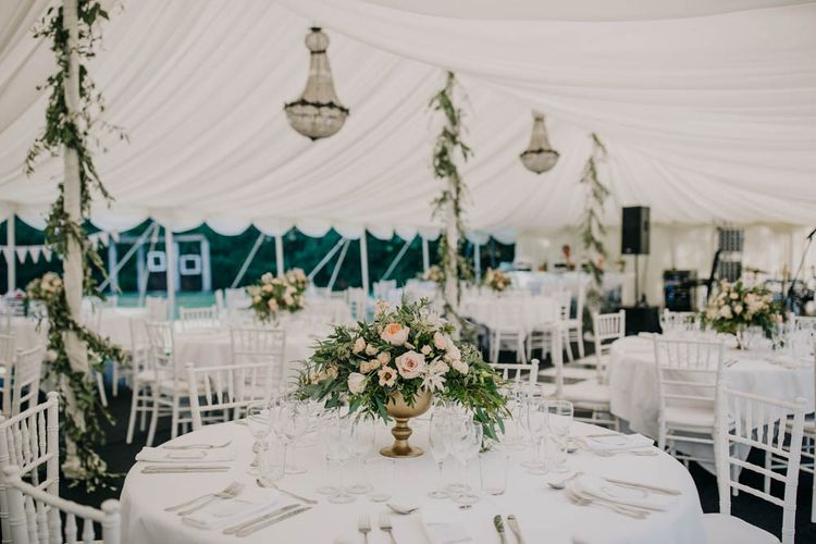 Table Centrepieces of Blush and White Flowers with Foliage in Gold Urns   Foliage Garlands Wrapped Around Marquee Poles   Gold Cutlery   Marquee with Open Side at Chateau La Durantie, Dordogne   Outdoor Seating Area and Macaroon Tower at French Chateau Wedding   Lush Imaging