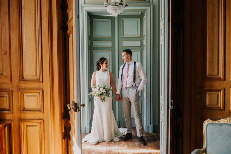 Bride in Lace Boat Neck Pronovias Wedding Dress with Keyhole Back and Fishtail Train   Bridal Bouquet of Blush and White Flowers with Foliage   Groom in Navy Braces, Grey Trousers and White Shirt with Pink Tie from Suit Supply   Chateau La Durantie, Dordogne   Outdoor Seating Area and Macaroon Tower at French Chateau Wedding   Lush Imaging