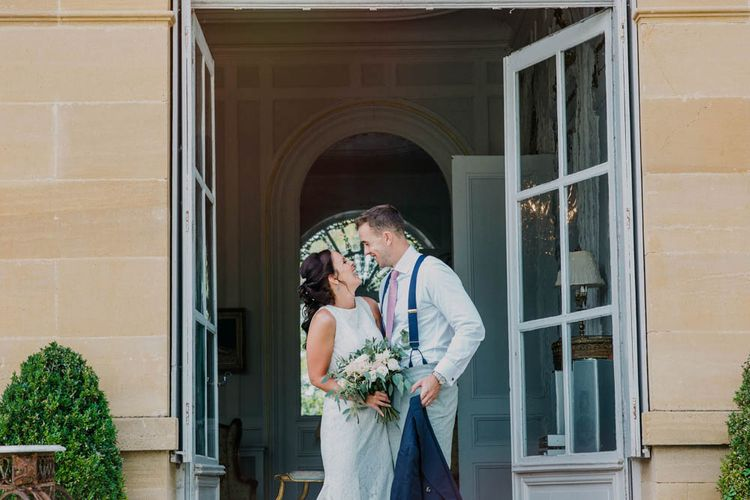 Bride in Lace Boat Neck Pronovias Wedding Dress with Keyhole Back and Fishtail Train   Bridal Bouquet of Blush and White Flowers with Foliage   Groom in Navy Jacket, Grey Trousers and White Shirt with Pink Tie from Suit Supply   Chateau La Durantie, Dordogne   Outdoor Seating Area and Macaroon Tower at French Chateau Wedding   Lush Imaging
