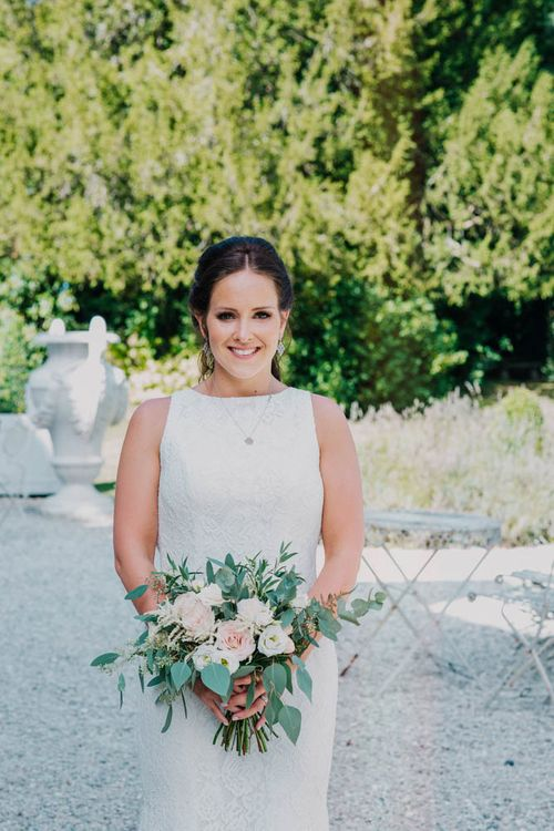 Bride in Lace Boat Neck Pronovias Wedding Dress with Keyhole Back and Fishtail Train   Bridal Bouquet of Blush and White Flowers with Foliage   Outdoor Seating Area and Macaroon Tower at French Chateau Wedding   Lush Imaging