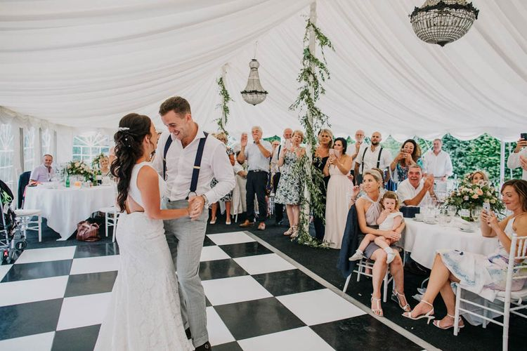 Bride in Lace Boat Neck Pronovias Wedding Dress with Keyhole Back and Fishtail Train   Groom in Navy Braces, Grey Trousers and White Shirt from Suit Supply   First Dance at Chateau La Durantie, Dordogne   Outdoor Seating Area and Macaroon Tower at French Chateau Wedding   Lush Imaging