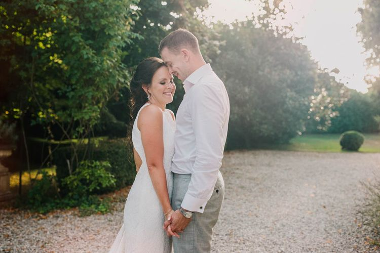 Bride in Lace Boat Neck Pronovias Wedding Dress with Keyhole Back and Fishtail Train   Groom in Grey Trousers and White Shirt from Suit Supply   Outdoor Seating Area and Macaroon Tower at French Chateau Wedding   Lush Imaging