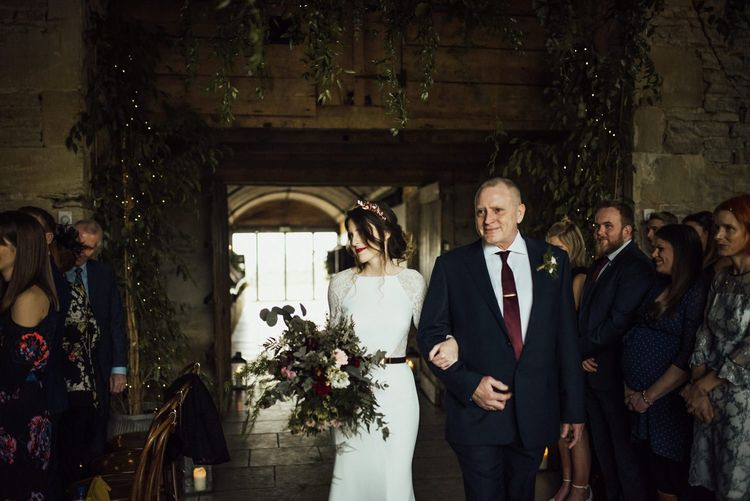 Stone Barn Wedding Ceremony Bridal Entrance in Fitted Wedding Dress with Lace Long Sleeves and Foliage Bouquet