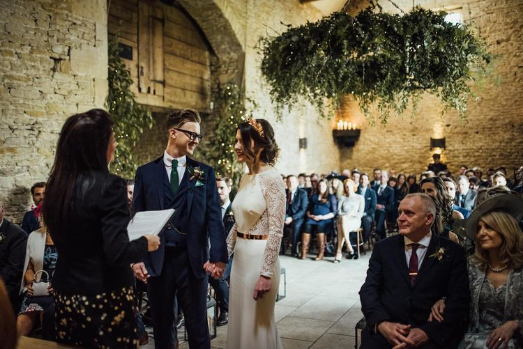 Bride and Groom Standing at Stone Barn Wedding Ceremony Holding Hands