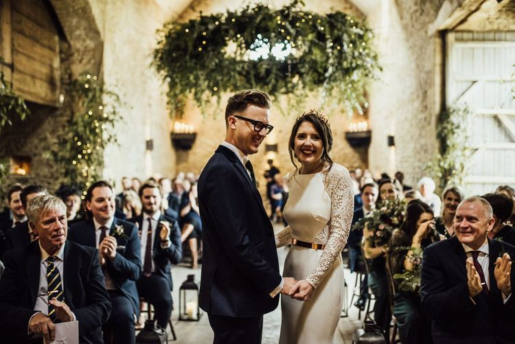 Bride and Groom Standing at Stone Barn Wedding Ceremony Holding Hands Laughing