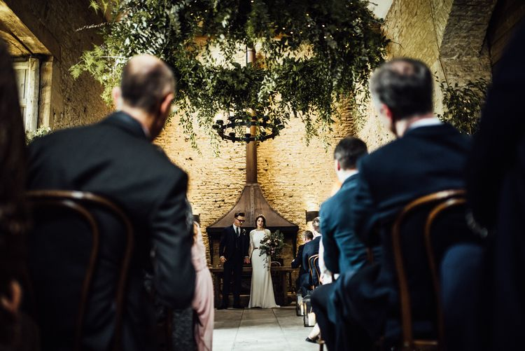 Bride and Groom Standing at The Altar of Stone Barn Wedding Venue in the Cotswolds