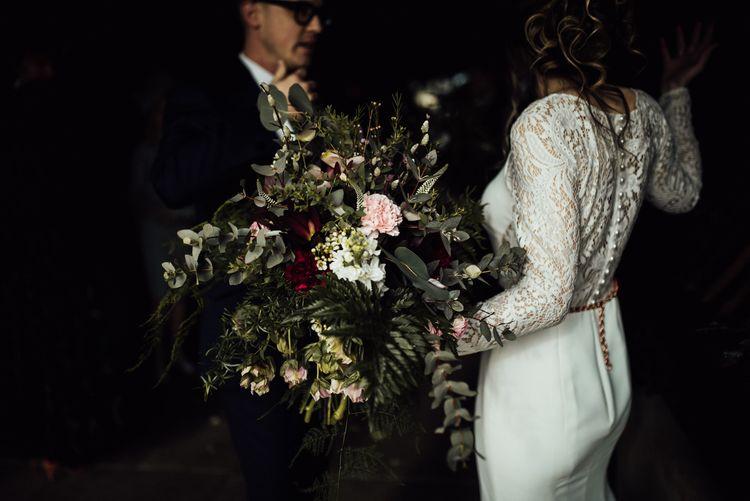 Bride in Lace Back Wedding Dress Holding Her Oversized Foliage Wedding Bouquet