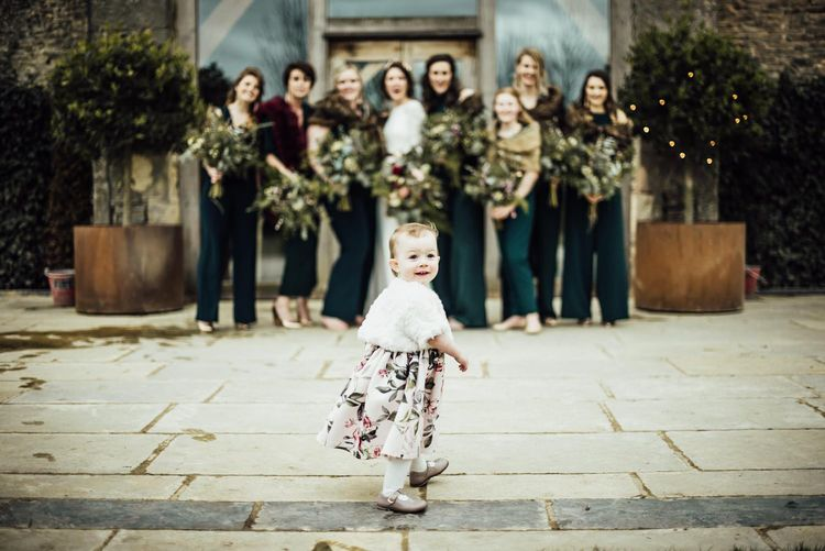 Flower Girl in Floral Dress Walking In Front of The Bridal Party