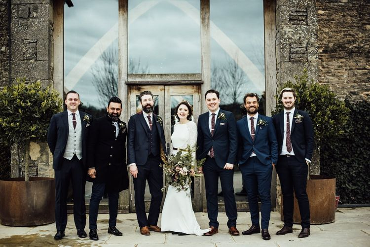 Bride in Fitted Wedding Dress Standing with the Groomsmen