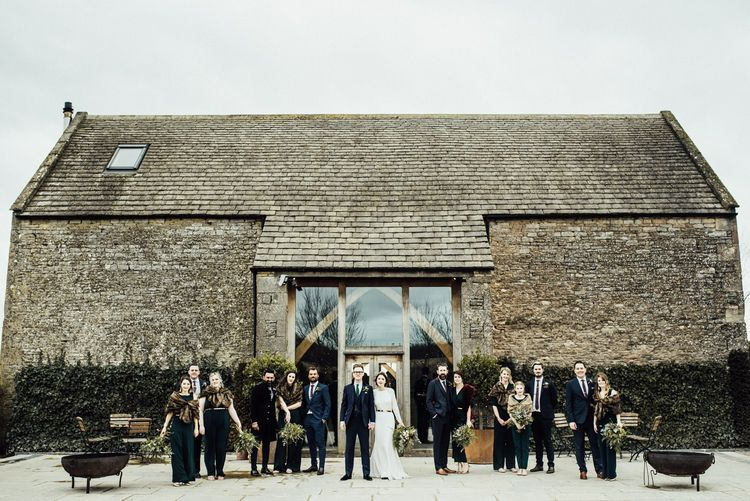 Winter Wedding Party Portrait Standing in Front  of Stone Barn Wedding Venue in the Cotswolds