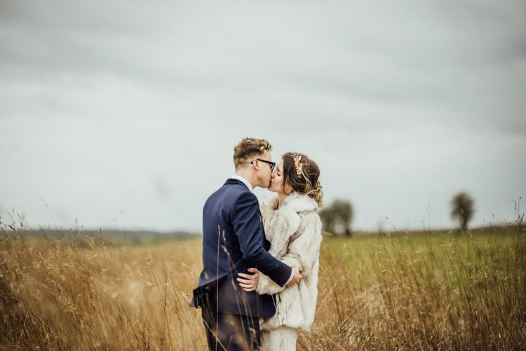 Bride in Faux Fur Coat and Groom in Navy Suit Kissing in the Fields