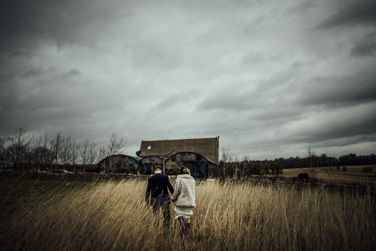 Bride and Groom Holding Hands Walking Through the Fields