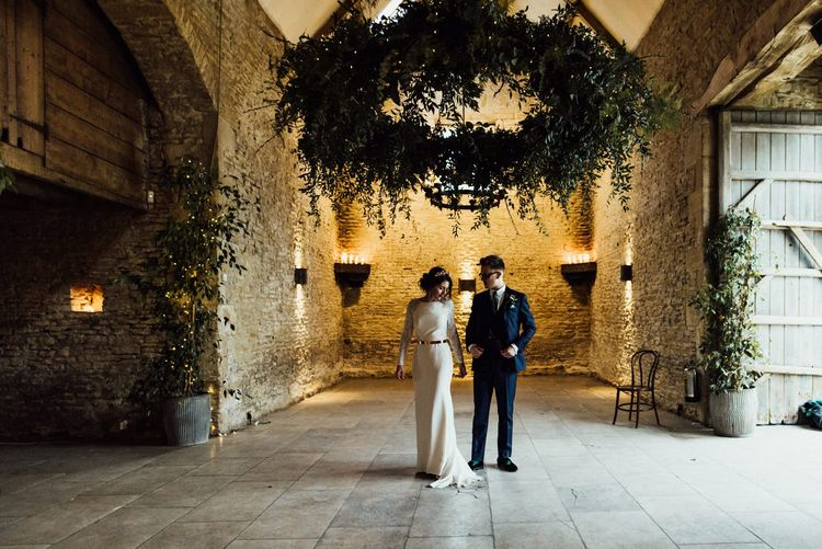 Bride in French By Wendy Makin Wedding Dress and Groom in Navy Blue Suit Holding Hands inside Stone Barn Cotswolds
