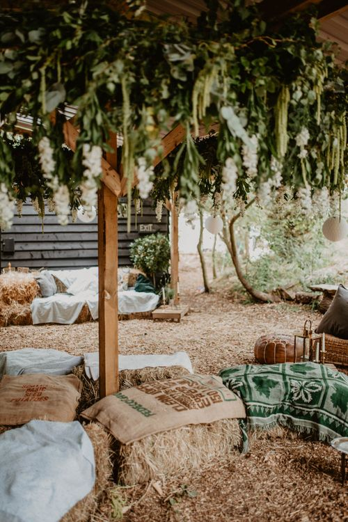 Hay bale Seating Area with Greenery Installation | Macramé & Dreamcatcher Woodland Wedding at Upthorpe Wood | Camilla Andrea Photography
