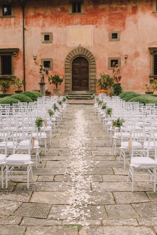 White Flower Petals Scattered Down Aisle with Chair Decoration