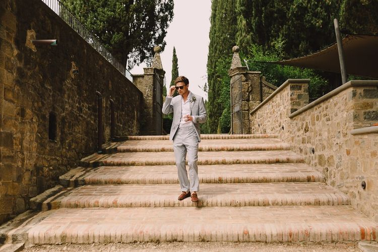 Groom in Pale Blue Suit from Canali with Sunglasses and Brown Leather Loafers