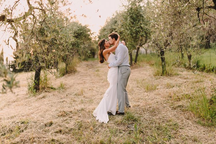 Bride and Groom Kiss in Fitted Bride Dress and Blue Groom Suit