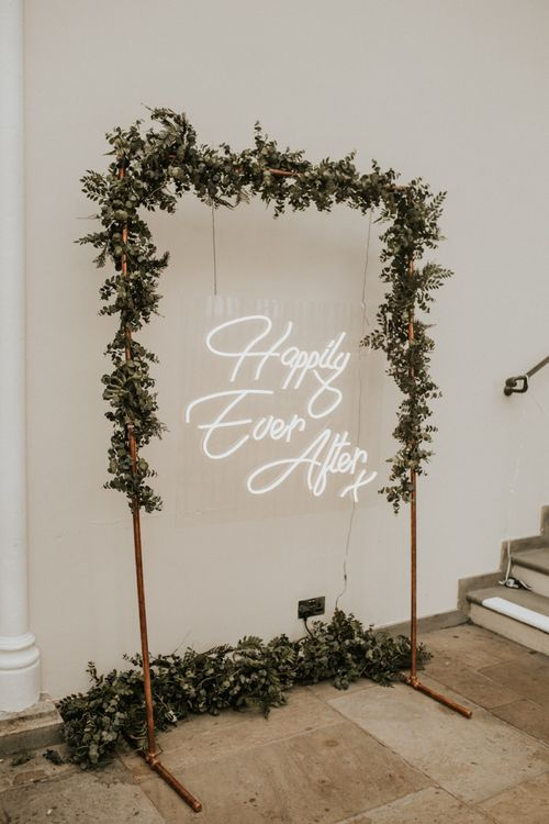 Happily Ever After White Neon Sign on Greenery Covered Copper Frame