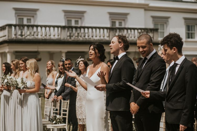 Wedding Party Signing During the Outdoor Wedding Ceremony