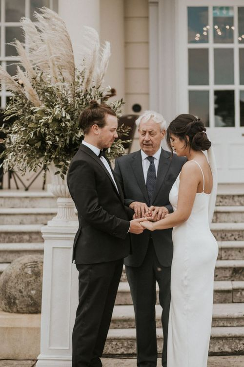 Bride in Grace Loves Lace The Arlo Slip Wedding Dress and Groom in Tuxedo Holding Hands During The Wedding Ceremony