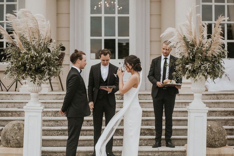 Bride in Grace Loves Lace The Arlo Slip Wedding Dress and Groom in Tuxedo Drinking During The Wedding Ceremony