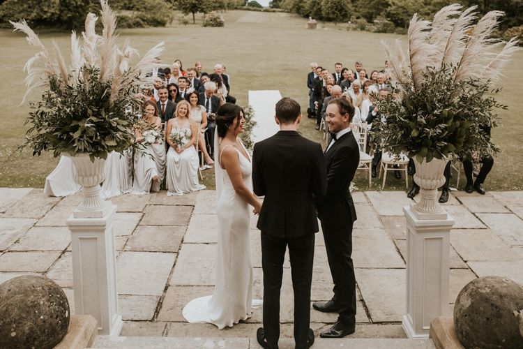 Bride in Grace Loves Lace The Arlo Slip Wedding Dress and Groom in Tuxedo Exchanging Vows During The Wedding Ceremony