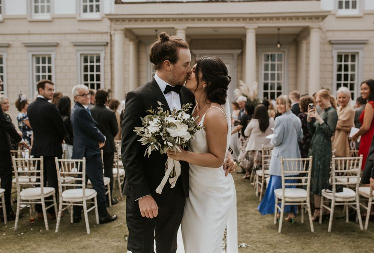 Bride in Grace Loves Lace The Arlo Slip Wedding Dress and Groom in Tuxedo  Kissing at the End of the Aisle