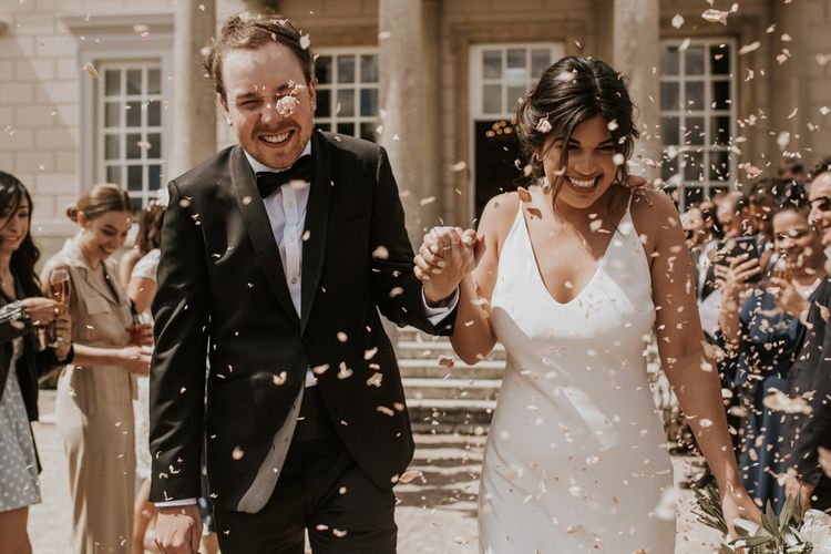 Confetti Moment with Bride in Grace Loves Lace The Arlo Slip Wedding Dress and Groom in Tuxedo