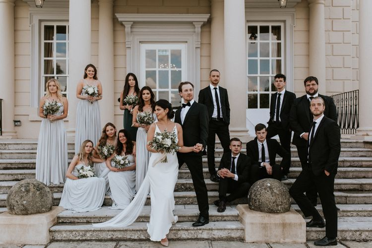 Sophisticated Group Wedding Party Portrait with Groomsmen in Tuxedo's and Bridesmaids in Grey Dresses