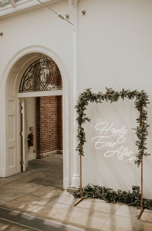 Happily Ever After White Neon Wedding Sign on Foliage Covered Copper Frame