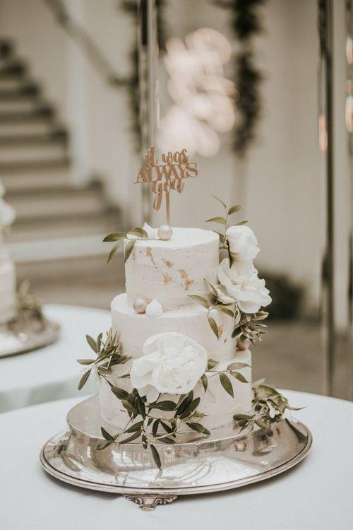 Elegant White Wedding Cake with Gold Detail and Foliage Decor