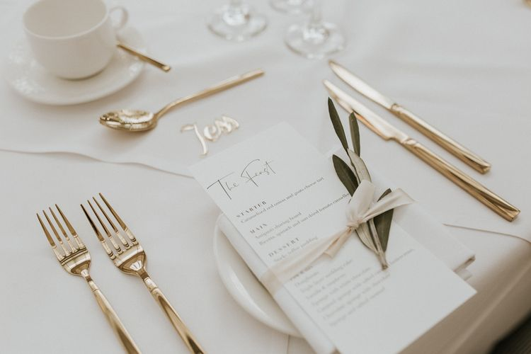 Place Setting with Gold Cutlery, Menu Card and Foliage