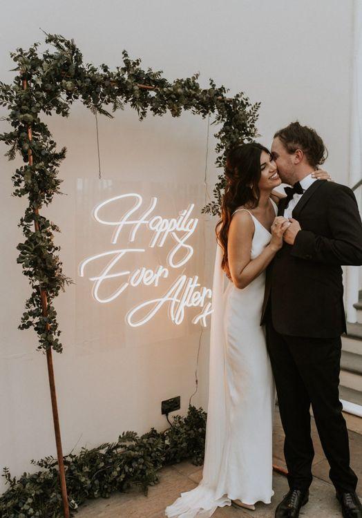 Bride in Slip Wedding Dress and Groom in Black Tie Suit Standing in Front of a Neon Wedding Sign