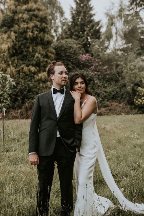 Bride in Slip Wedding Dress Embracing Groom in Black Tie Suit