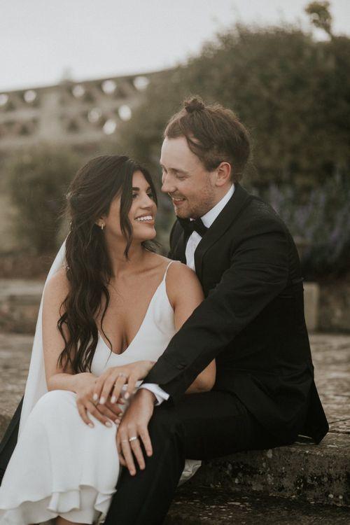 Groom in Black Tie Suit Embracing His Bride in Slip Wedding Dress