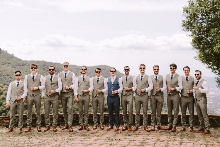 Groom with groomsmen in matching cream waistcoats at destination wedding