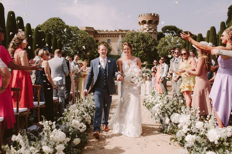 Confetti exit for bride in Essense of Australia wedding dress and groom in blue suit