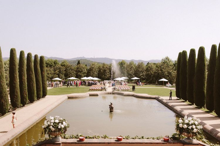Guests enjoy drinks in the gardens of Castell de Sant Marçal