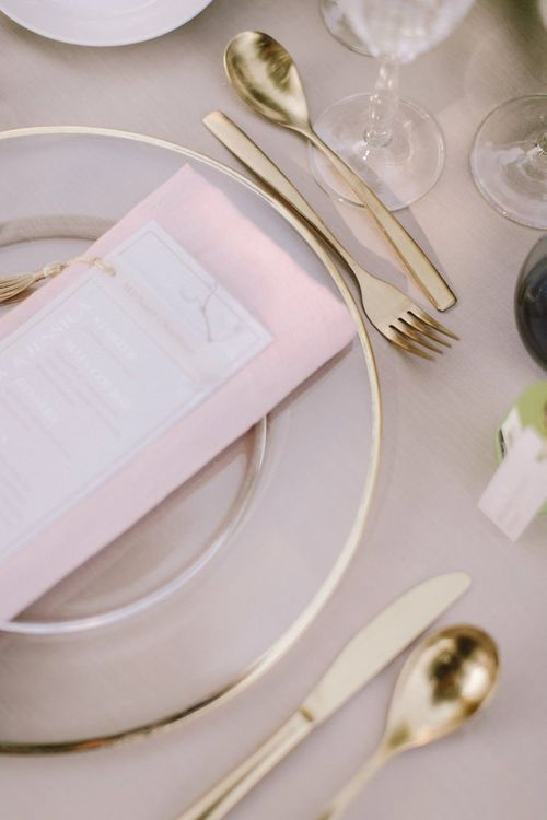 Wedding table place setting with pink detail and gold cutlery