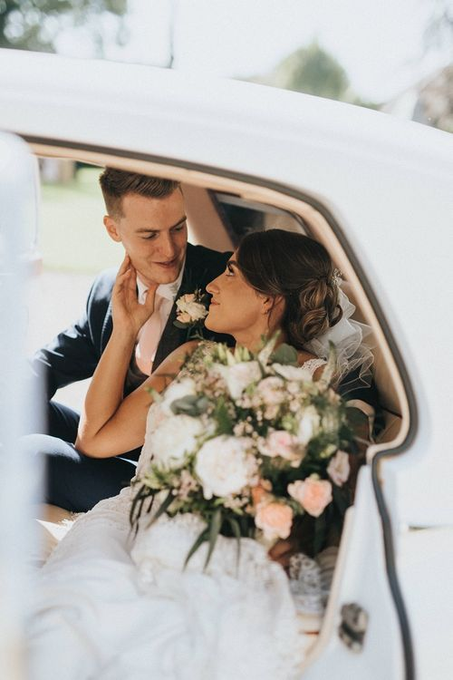 Bride and groom in wedding car with blush bouquets