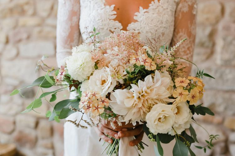 Bride in Nicole Spose Lace Wedding Dress Holding a Pale Pink and White Bouquet of Roses and Dahlias