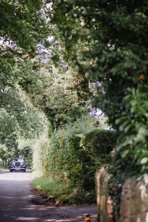 Classic Wedding Car Driving Down the Country Lane