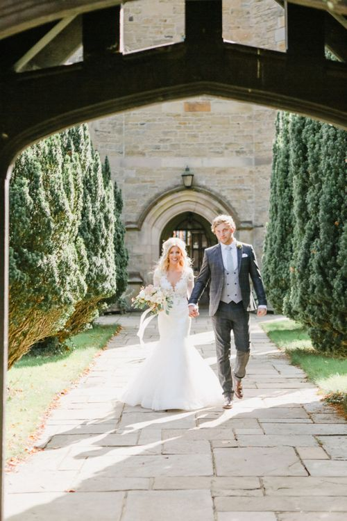 Bride in Lace Fishtail Nicole Spose Wedding Dress and Groom in Blue Check Most Suitable Suit