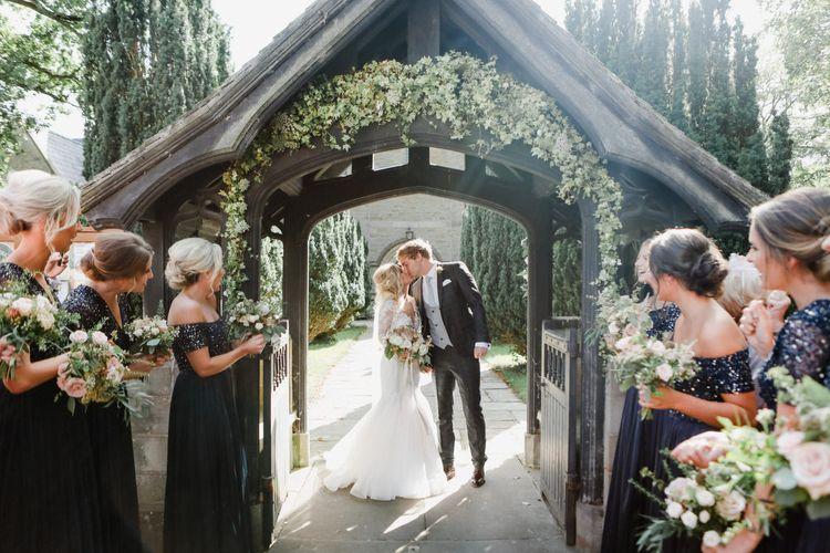 Bride and Groom Kissing Under The Church Courtyard Arch Decorated with Wedding Flowers