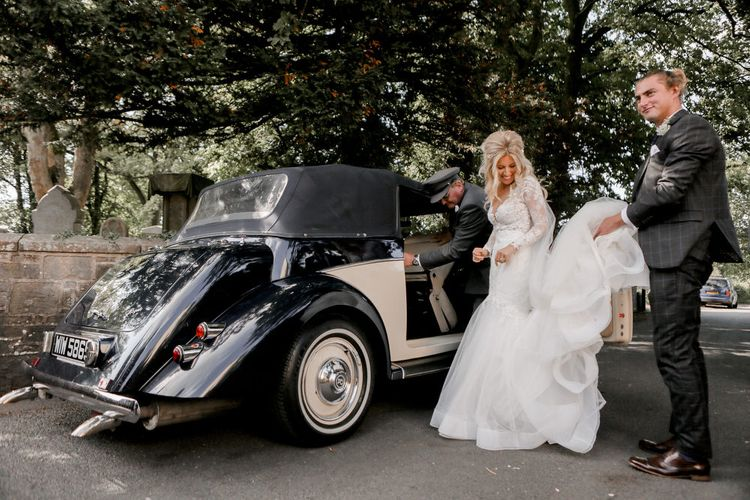 Groom Helping His Bride with Her Wedding Dress Getting in to the Classic Wedding Car